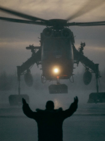 A Man Guides a Landing Helicopter